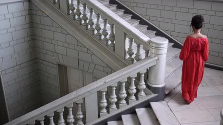 wall building feature : elegant actress in red dress on high heels climbs a large staircase at beautiful hall, top view