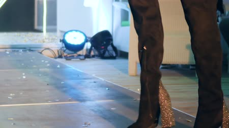 süet : womens legs in black suede boots on high shiny heel go along podium on fashion show close-up