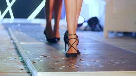 sandals : slim feet of girl in Stylish black sandals walking along podium on fashion week close-up in unfocused