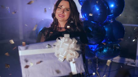 ringlet : gift box with bow in hands of happy female amid sparkling confetti and fog against backdrop of inflatable balloons in backlight