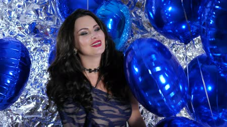 ringlet : festive mood, happy female with blue inflatable balloons in hands near wall decorated with foil Stock Footage