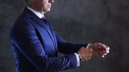 nákrčník : watch and engagement ring on hands of male which refills sleeves of shirt in jacket on background gray concrete wall