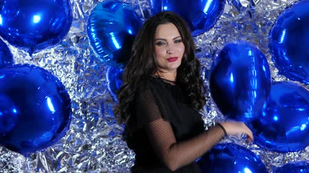 ringlet : merry brunette with evening make-up among bright inflatable balloons on background of shiny wall at event