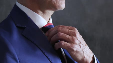 nákrčník : mens arms adjust blue necktie on throat close-up against gray wall, side view