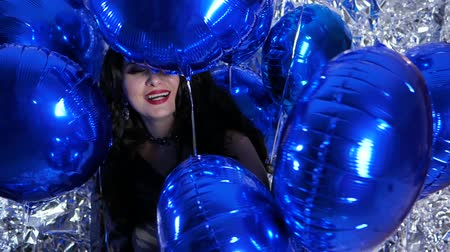 ringlet : joyful woman in good mood among inflatable balloons on background of shiny wall at evening event