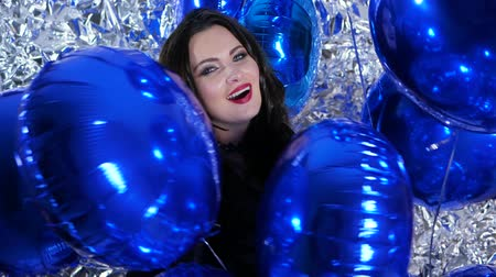 ringlet : happy emotional women with blue balloons in arms on background shiny wall decorated with foil