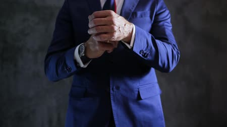 nákrčník : elegant fashionable suit of man which corrects sleeves, engagement ring and wristwatch on arms close-up against gray wall Dostupné videozáznamy