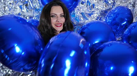 ringlet : blue balloons in hands of beautiful lady with red lips on background sparkling wall