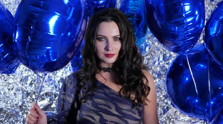 ringlet : birthday, lot of vivid balloons in hands of emotional female with red lips on background silver wall Stock Footage