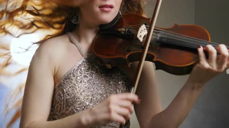 podfuk : female person emotionally plays on fiddle closeup indoors philharmonic society on background of bright light and smoke Dostupné videozáznamy