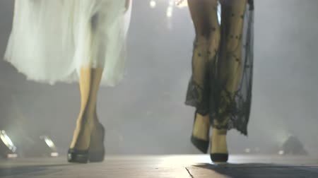 high heel shoe : slim silhouettes of models go along the catwalk during a fashion show on background of lights and smoke Stock Footage