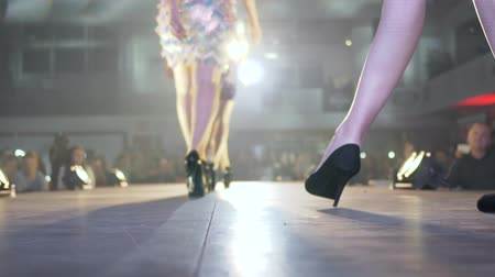 неделя : models in shoes on high heels go along runway on background of bright lights at fashion week
