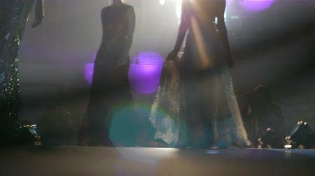 подиум : models in chic evening dresses close-up posing on catwalk on background of smoke and light Стоковые видеозаписи