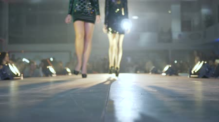 high heeled shoe : female feets on high heels walk on the model podium in slow motion in spotlight at fashion show