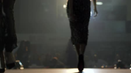 podium : fashion business, models in chic dresses at the catwalk in light of the cameras on a blurred background