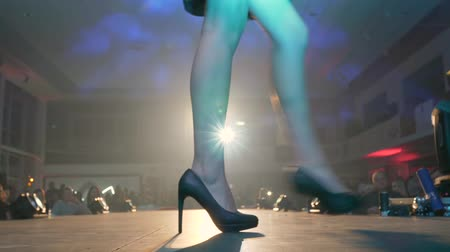 high heeled sandals : fashionable entertainment, womens legs on high-heeled go in row through stage in bright spotlights
