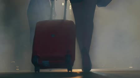 high heeled sandals : travel suitcase in hands of model of podium in high heels in thick smoke close-up