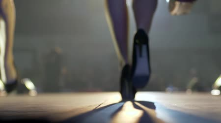 high heeled sandals : professional model in comfortable shoes with bag into hand goes on podium at illumination of lamps in unfocused background Stock Footage