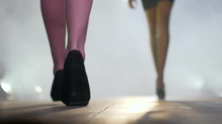 high heeled sandals : fashion week, beautiful woman feet in black footwear go down catwalk in thick haze Stock Footage
