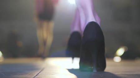 high heeled sandals : fashion show, models on high heels are walking along catwalk on unfocused background Stock Footage