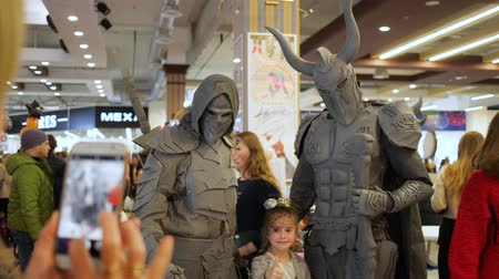 greasepaint : Kherson, Ukraine 31 October 2017: warriors in masks and armor posing with little girl for photos in mall at the Halloween celebration in Kherson, 31 October 2017.