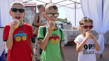 cümbüş : Kherson, Ukraine 9 September 2017: company of happy friends in sunglasses licking ice cream in Kherson, 9 September 2017.