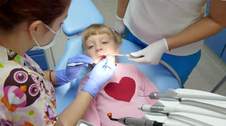 spolupracovníci : little patient open-mouthed lies on dental chair at treatment with specialist with tools in arms and gives thumbs-up in hospital