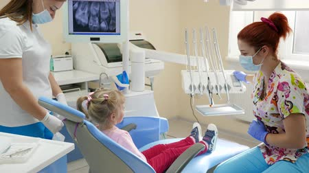 spolupracovníci : little girl came to stomatologist and sits down in dental armchair next to instruments and equipment in bright office