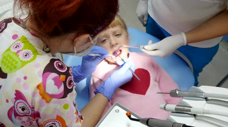 spolupracovníci : happy girl on dental inspection with professional dentist in rubber gloves with tools close-up, view from above Dostupné videozáznamy