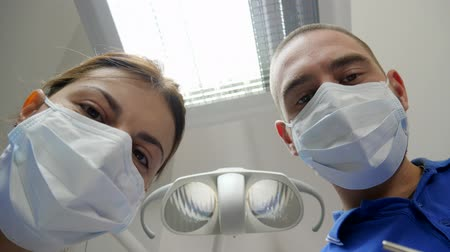 estéril : doctor and assistant in medical masks close-up during visit of customer, patient point of view