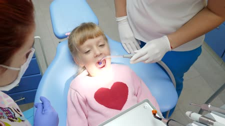 spolupracovníci : child with open-mouthed lies on dental armchair at treatment by doctor with instruments in hands in clinic close-up