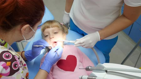 spolupracovníci : Medicine and health care, child with aching teeth lies on dental armchair at treatment with doctor with instruments in hands in dentists office Dostupné videozáznamy