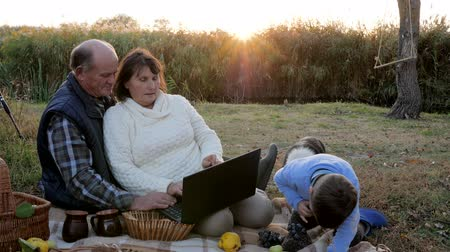 use laptop : picnic on sunrise, attractive happy mature couple with grandson and pet sits at plaid with laptop Stock Footage