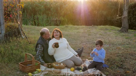 ježek : old people with grandson enjoying picnic on nature against the background of a sunset and river