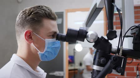 állapot : specialist in medical mask looks through optical microscope close-up in laboratory