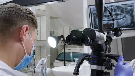 lab employee : men specialist works with optical microscope in front of jaw on monitor in dentists modern office