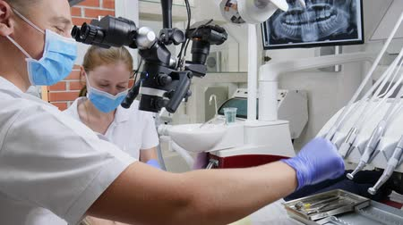 spolupracovníci : medical workers use dental microscope for treatment of patients teeth in hospital with modern hardware
