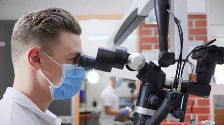 lab employee : medical worker in medical mask looks through optical microscope close-up in lab