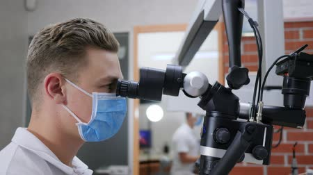 lab employee : Laboratory researcher in medical mask looks through microscope close-up in clinic Stock Footage