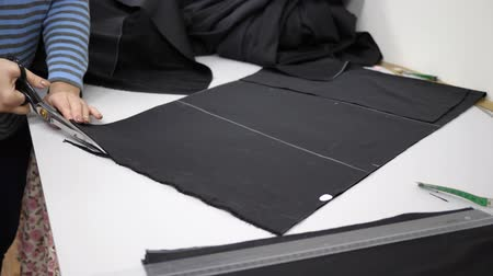 roupagem : textiles, worker of atelier cuts black fabric on white table close-up Vídeos