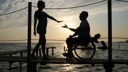 alfândega : silhouette of loving couple with disabled person met on seafront near shiny water in bright beams