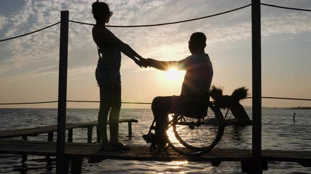 alfândega : silhouette of Lovers on wheelchair standing to quay holding hands on background of water and sky in sunset Stock Footage