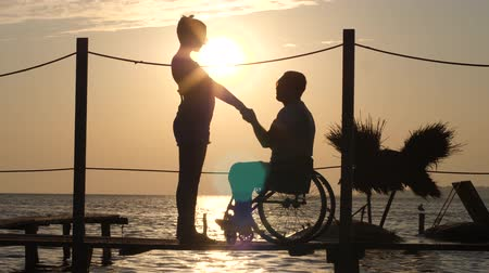 alfândega : silhouette of female and male handicapped on wheel chair holding arms and look at orange horizon at pier in sea