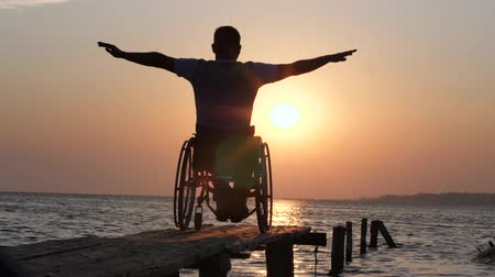 alfândega : sick guy is sitting in wheel chair and lift his arms backdrop of evening sun and orange heaven near water on seacoast on summer holiday