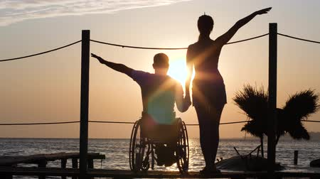 alfândega : man disabled with girlfriend holding hands in romantic date to ocean in Sun rays of orange afterglow