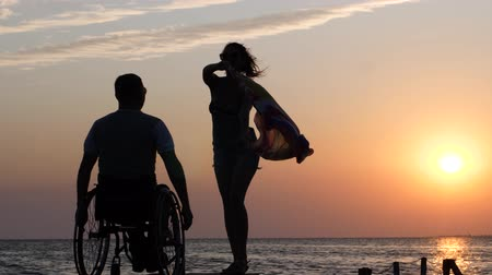 alfândega : disabled person living a full life woman is standing on jetty and waving a cloth in front of guy crippled into wheelchair on background of orange sundown over river at summer holiday.