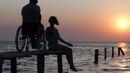 alfândega : disabled person living a full life, laughing girl in sunglasses sitting on wooden pier and talking with man disabled in wheelchair backdrop of sunset and sea water