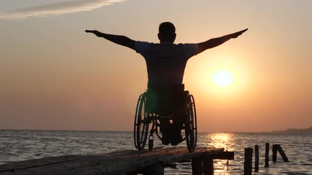alfândega : disabled person living a full life man in wheelchair relaxes and lift his hands backdrop of orange sky near water on Embankment on summer trip