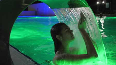 artificial color : Pleasure of Young Woman on Summer rest under Artificial waterfall of night pool at resort Stock Footage