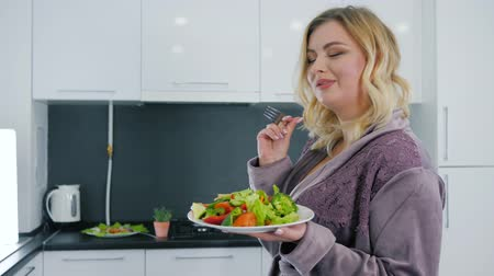 girl in robe : full woman dreams of a slender figure young female eats healthy food at kitchen in sexy robe and drinks water from glass Stock Footage